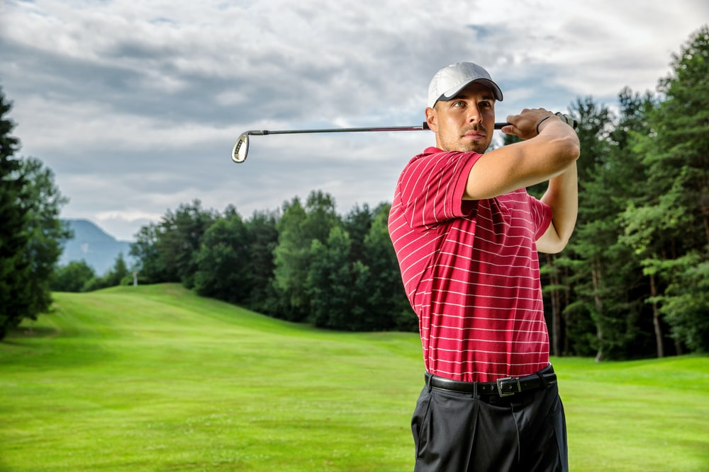 man in red and white plaid shirt and black pants holding golf club