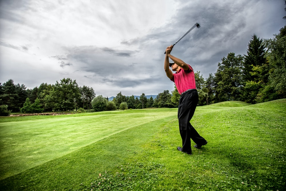 man in red t-shirt and black pants playing golf during daytime