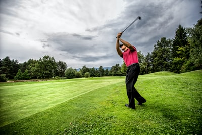 man in red t-shirt and black pants playing golf during daytime golf teams background