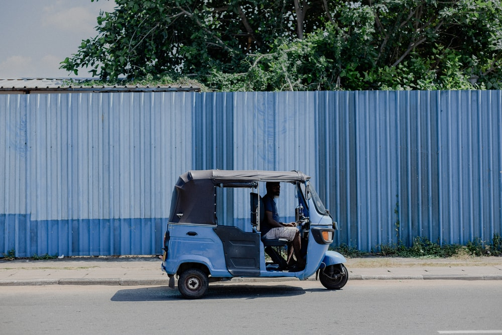 blue and white auto rickshaw parked beside white wall
