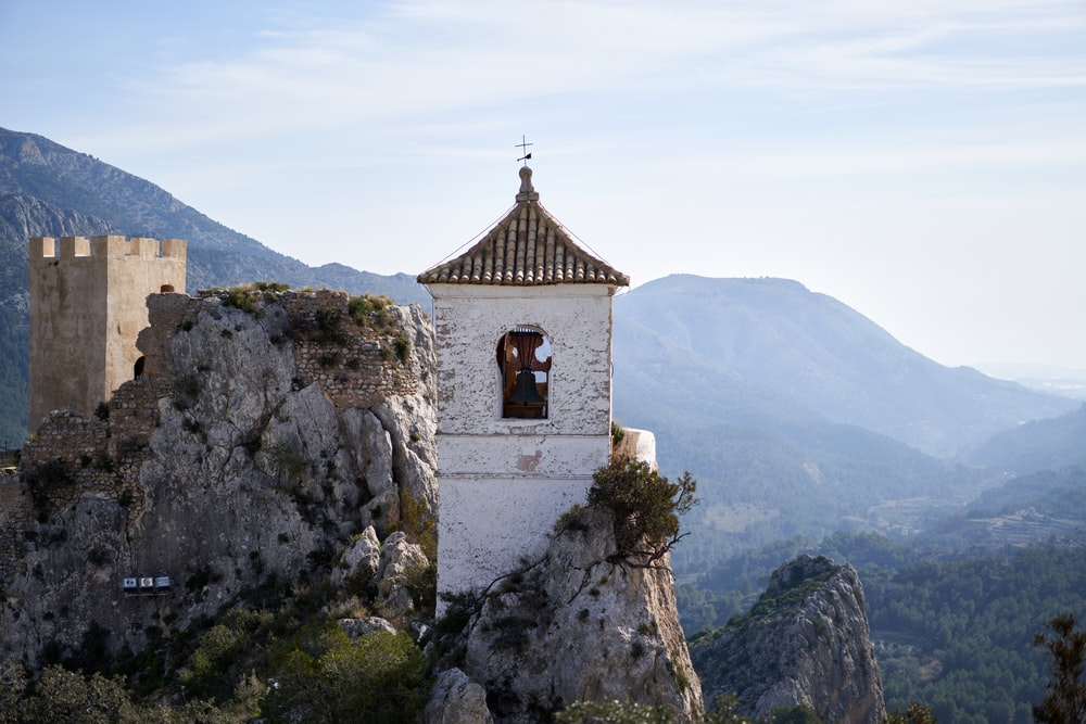 brown and white concrete church on top of mountain during daytime