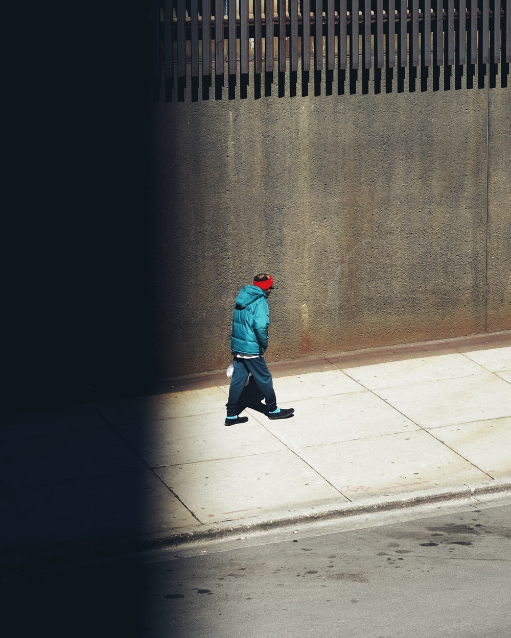 person in green hoodie walking on sidewalk during daytime