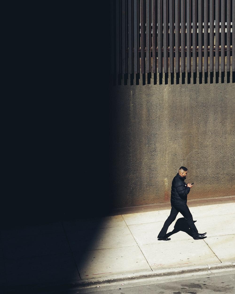 man in black jacket walking on brown floor