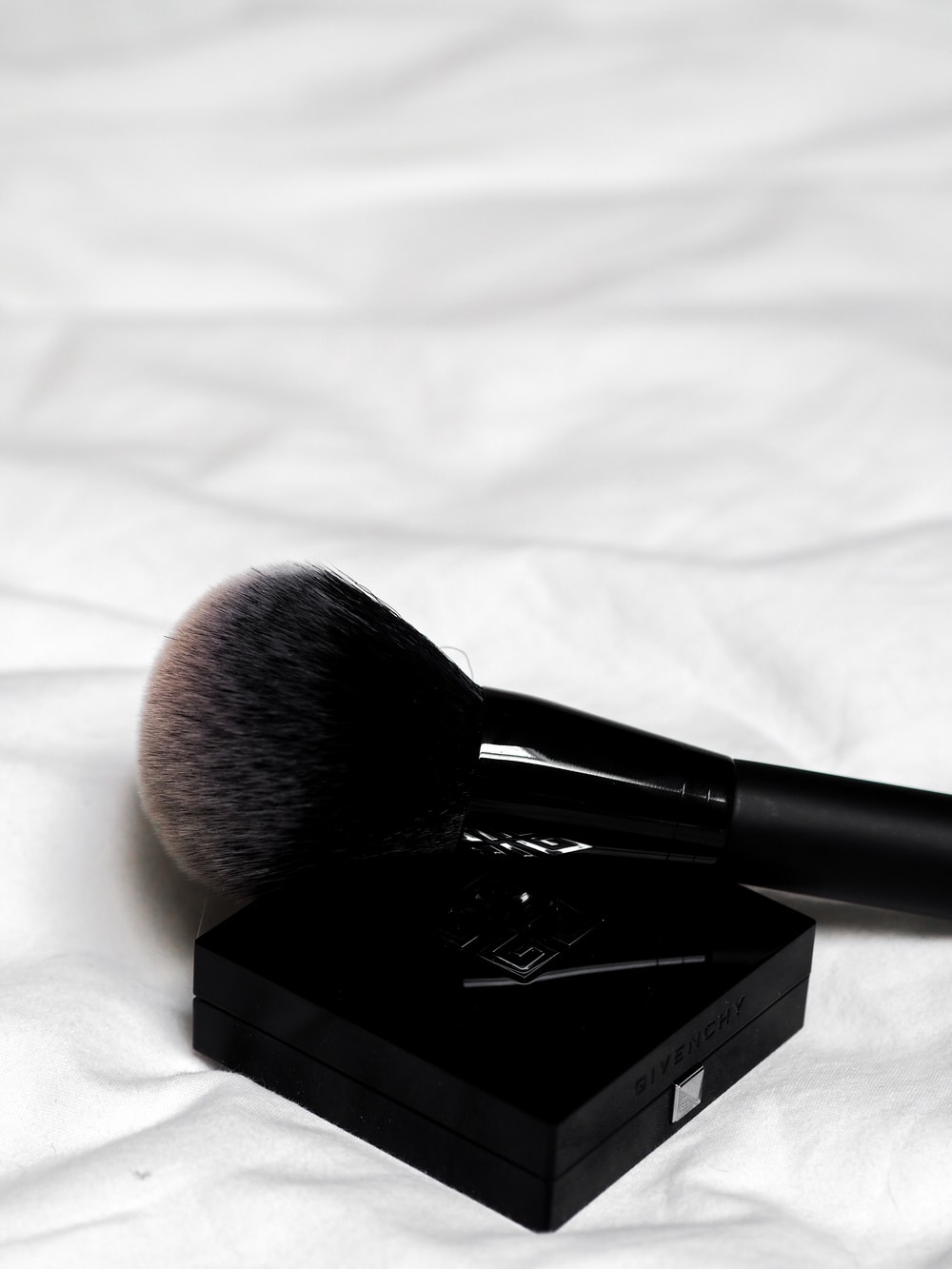 black make up brush on white textile