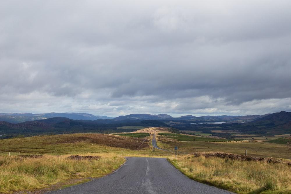 black asphalt road between green grass field under white cloudy sky during daytime