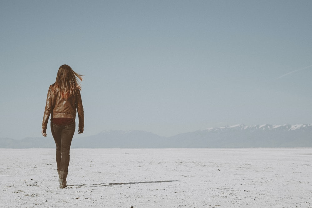 woman in brown jacket standing on white snow covered field during daytime