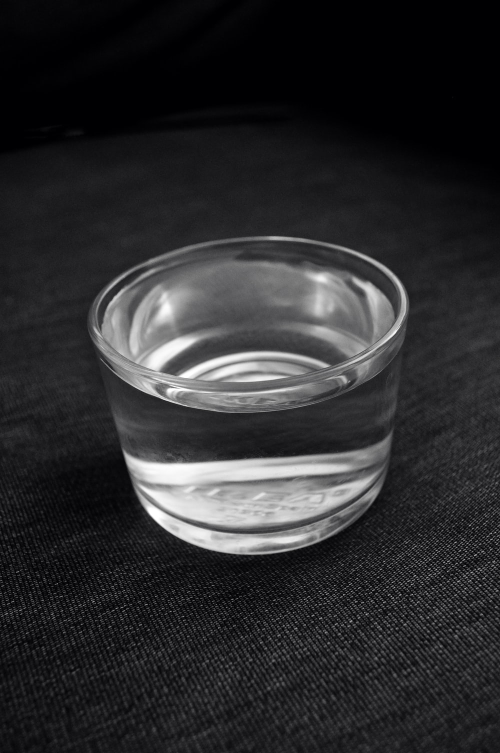 clear drinking glass on black textile