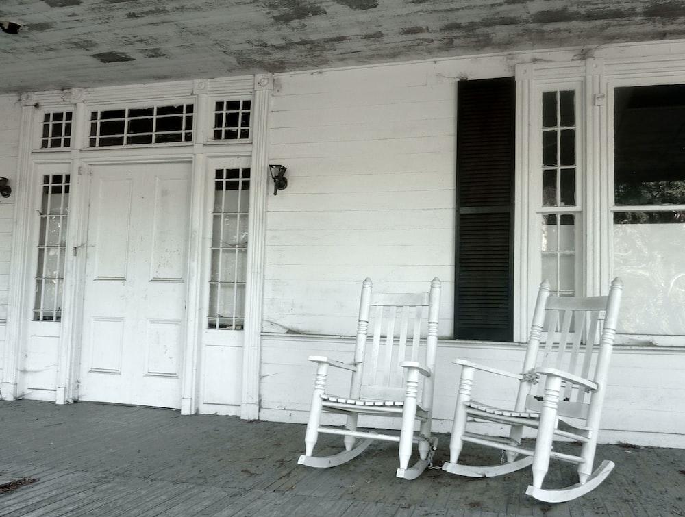 white wooden rocking chair beside white wooden door