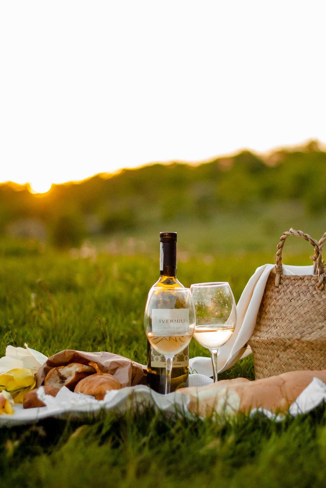 A picnic on the grass at sunset - containing pastries and a bottle of rosé wine