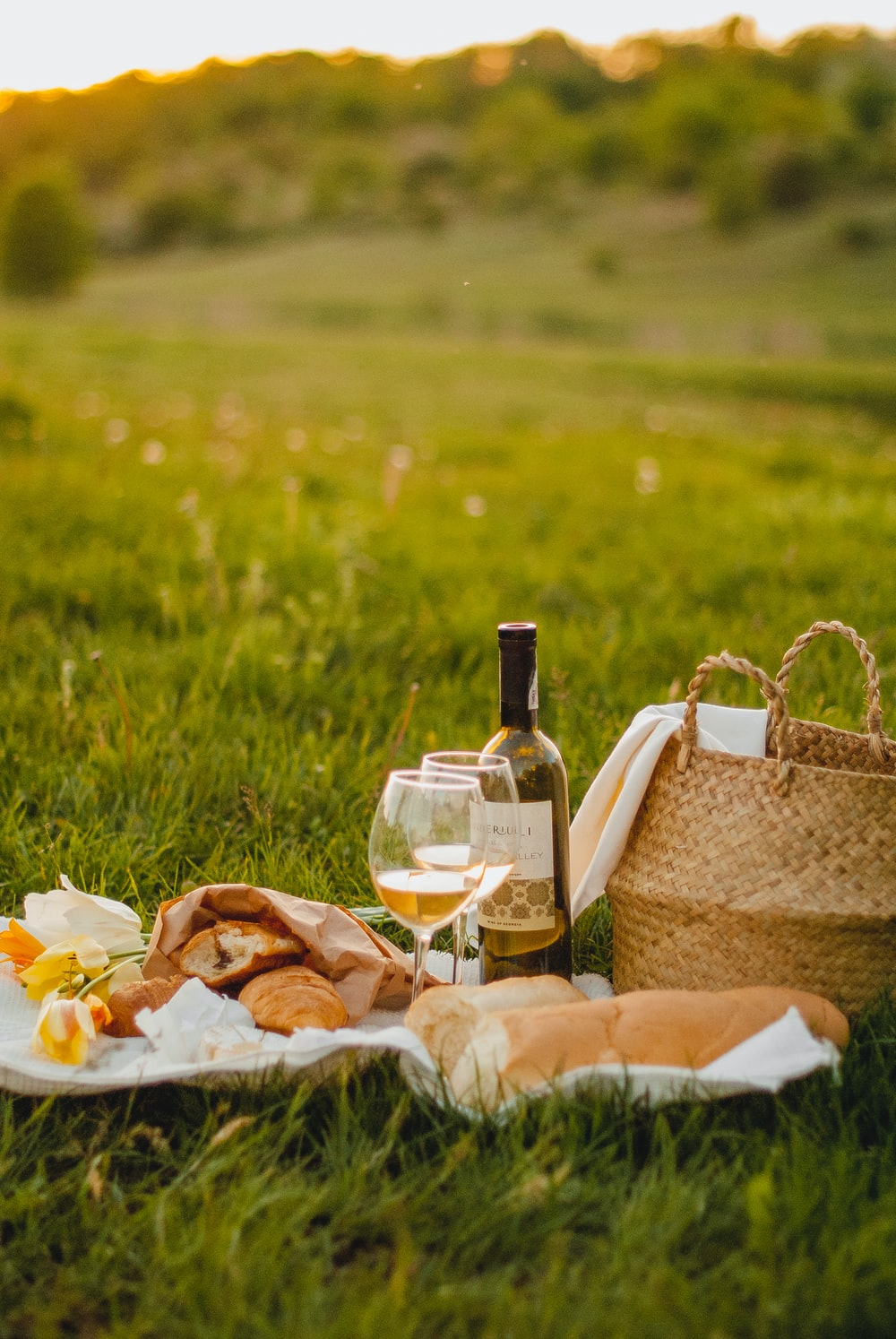 clear glass bottle beside brown wicker basket on green grass during daytime