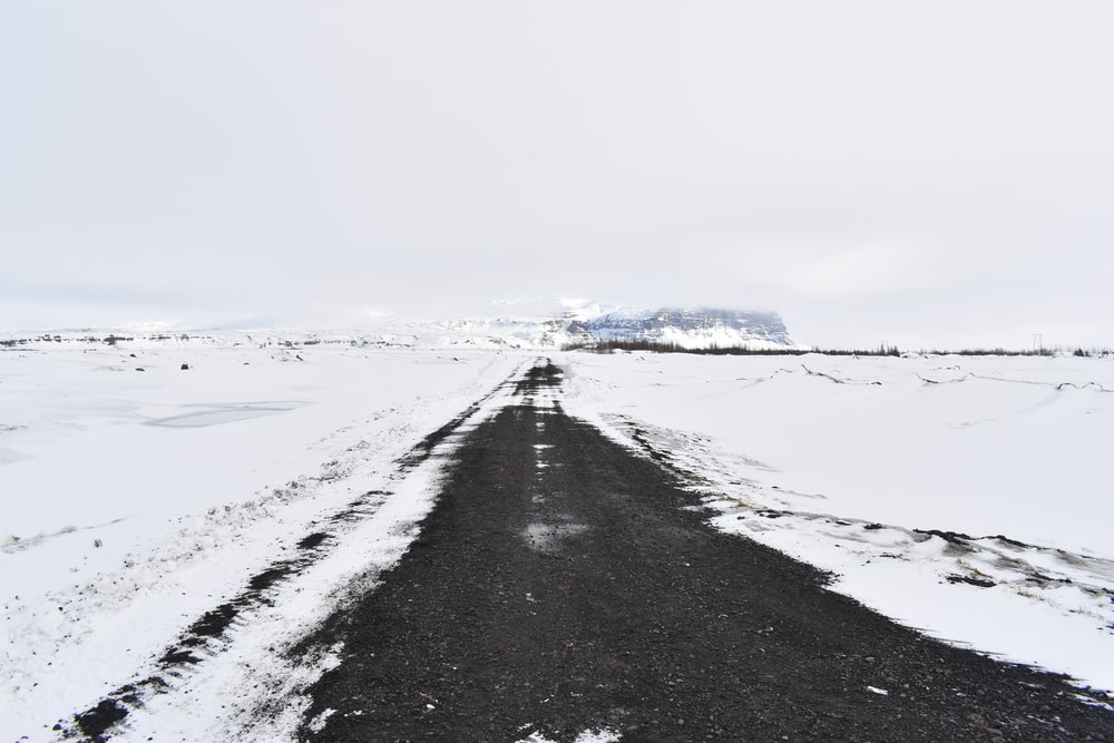 black asphalt road covered with snow