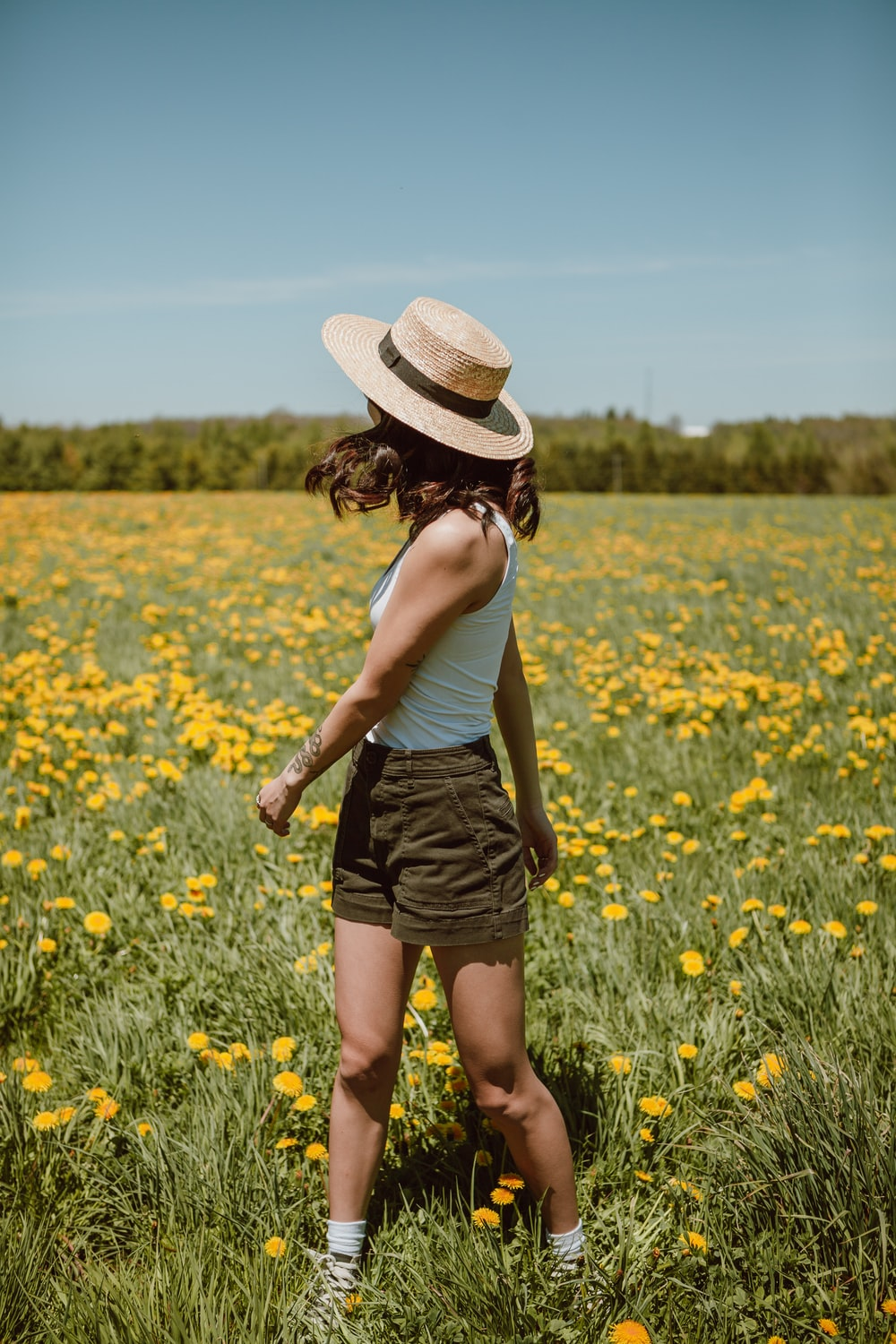woman in white tank top and black skirt standing on yellow flower field during daytime