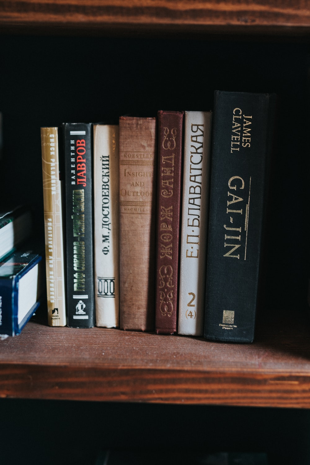black and brown books on brown wooden shelf