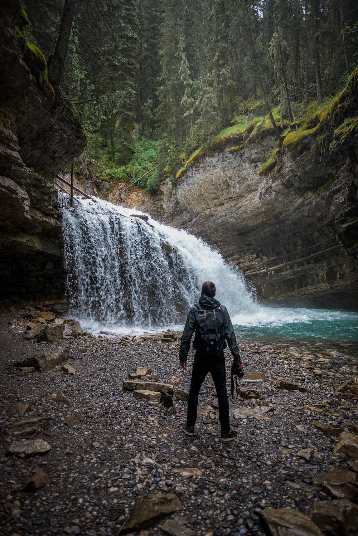 man in black jacket standing near waterfalls during daytime