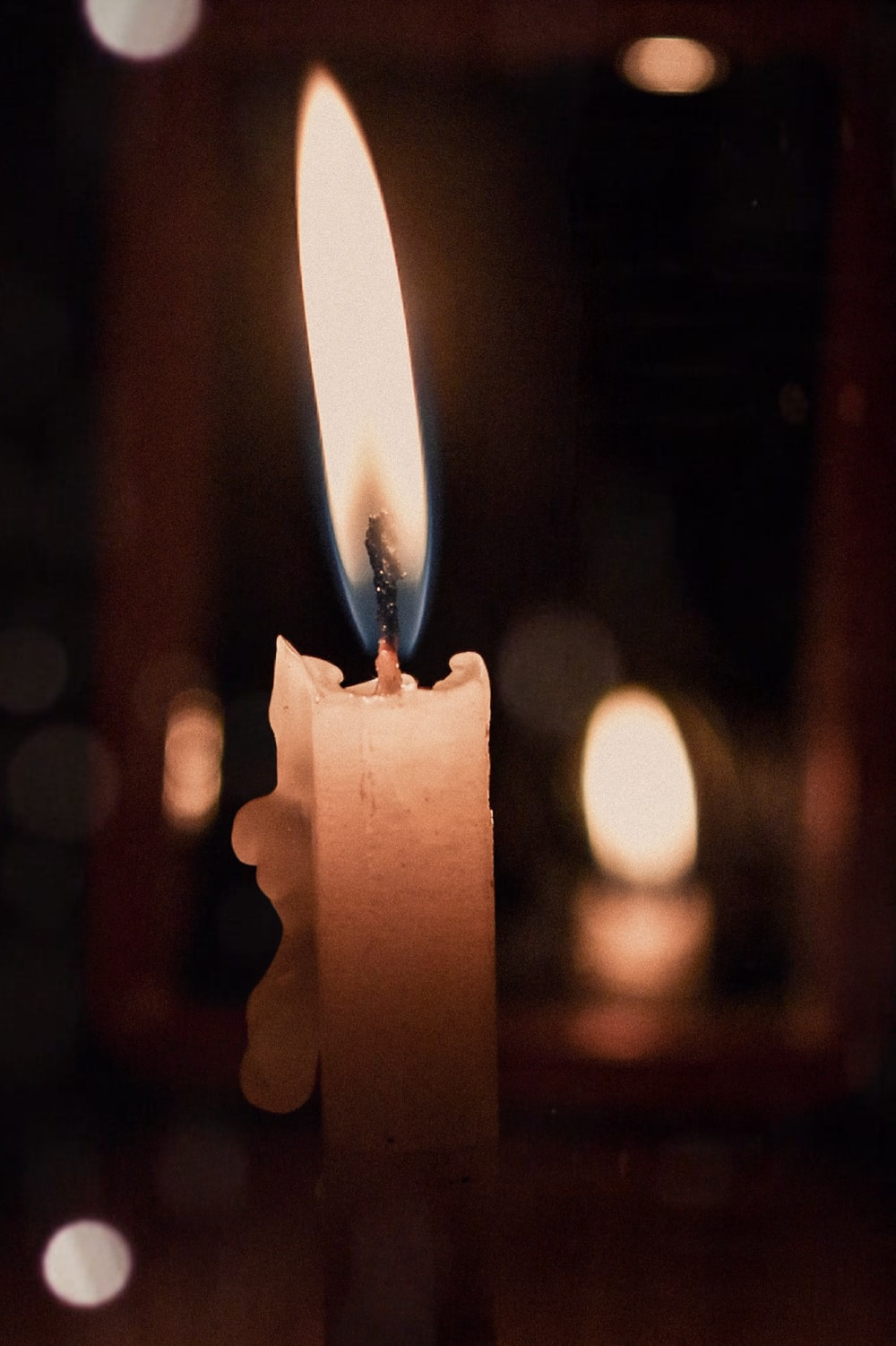 white candle with fire in tilt shift lens