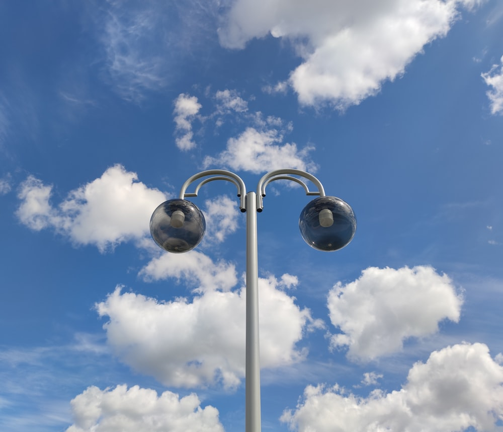 silver street light under blue sky and white clouds during daytime