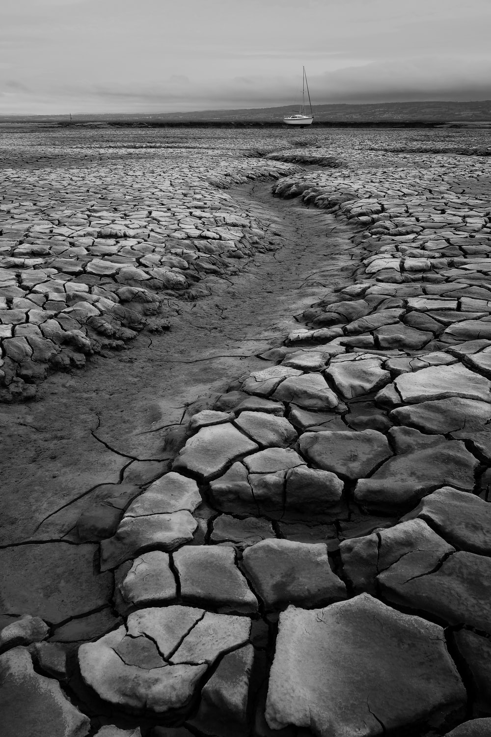 grayscale photo of water on sand