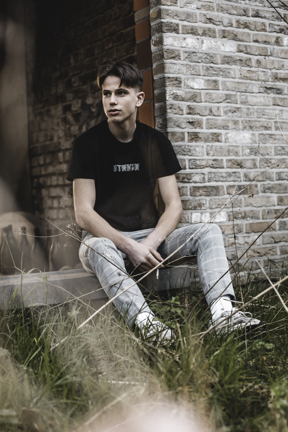 man in black crew neck t-shirt and blue denim jeans sitting on green grass during