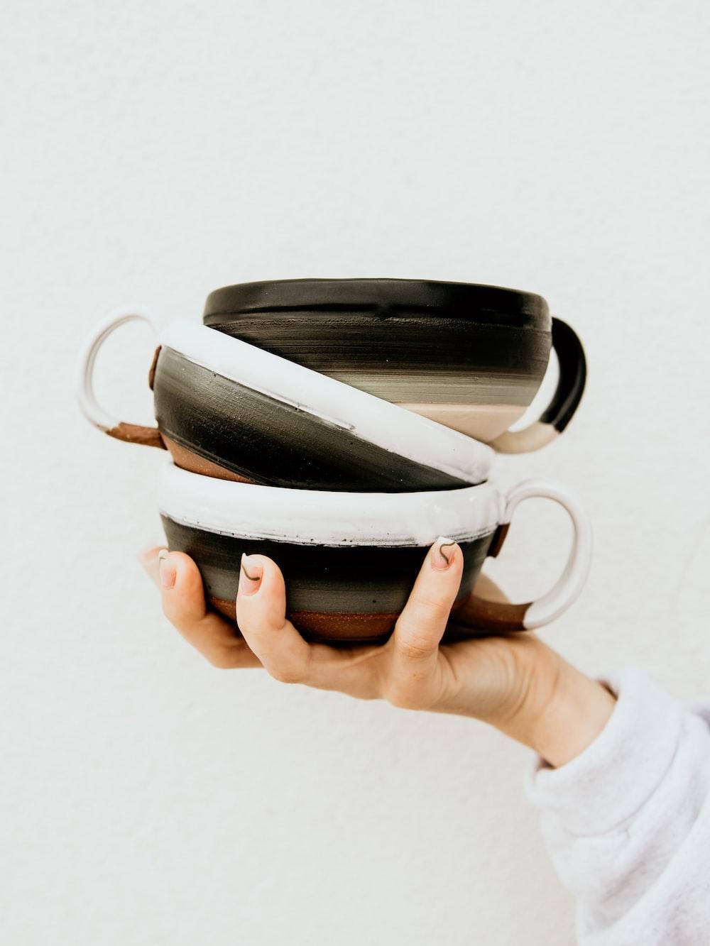 person holding black and white ceramic mug