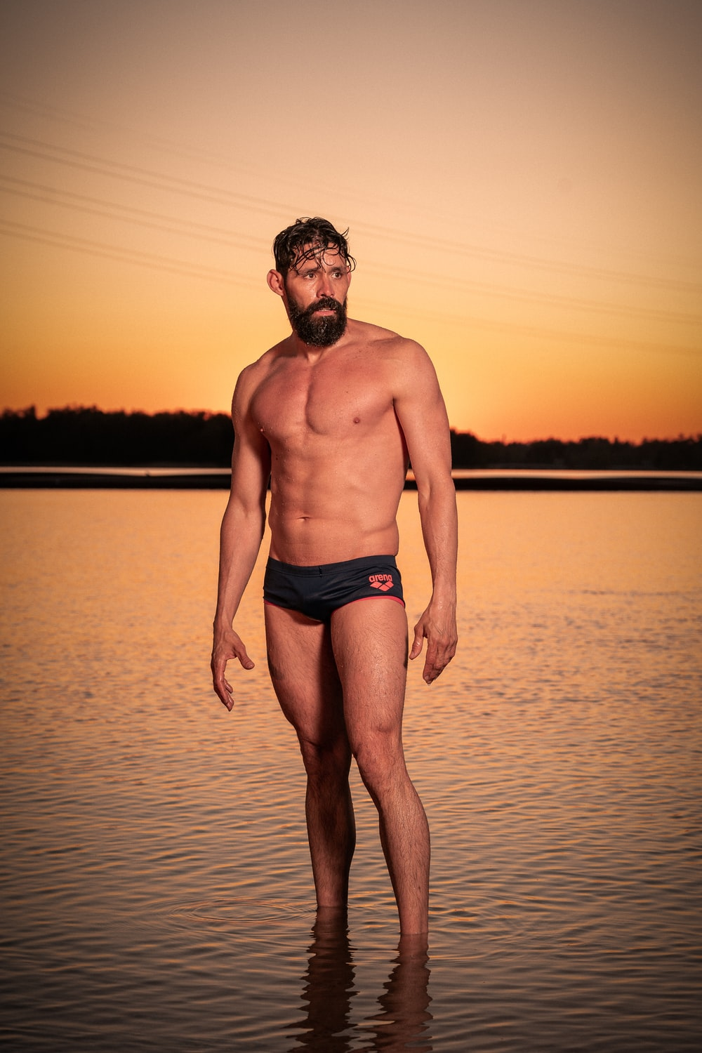 man in blue brief standing on water during sunset