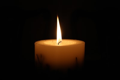 white candle in black holder candle teams background