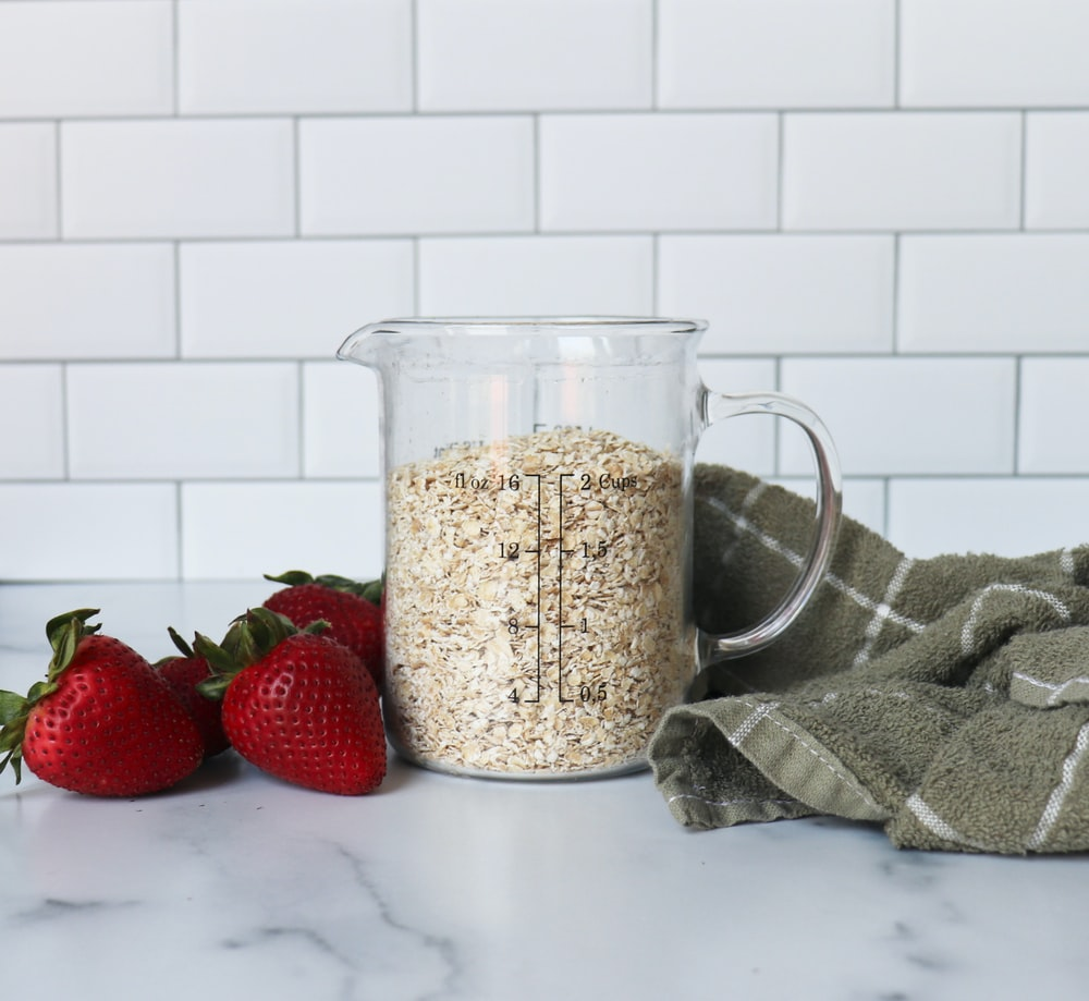 strawberries on white ceramic bowl beside clear glass pitcher