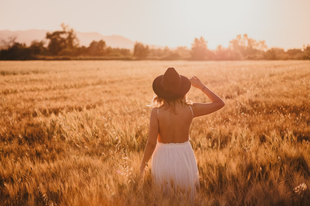 woman in white dress wearing brown hat standing on brown grass field during daytime