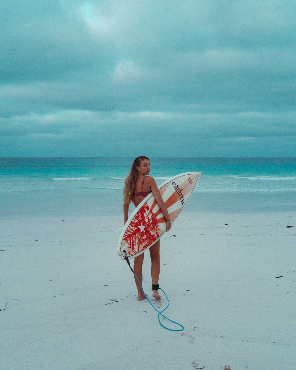 woman in white and red floral dress holding white and red surfboard on beach during daytime