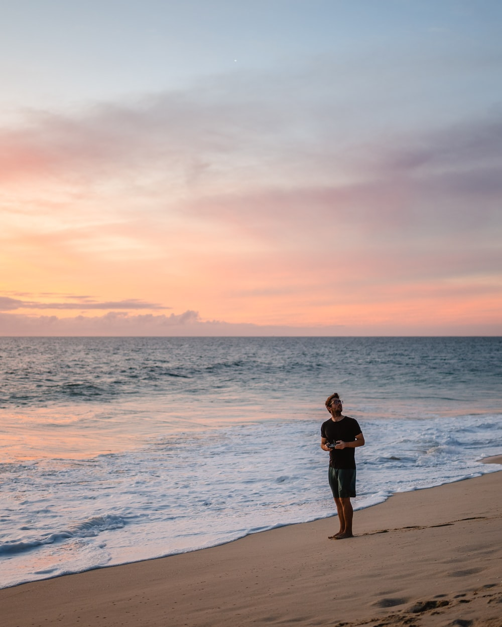 woman in black dress standing on beach during sunset