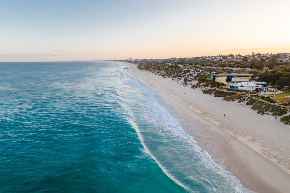 blue sea beside white sand during daytime