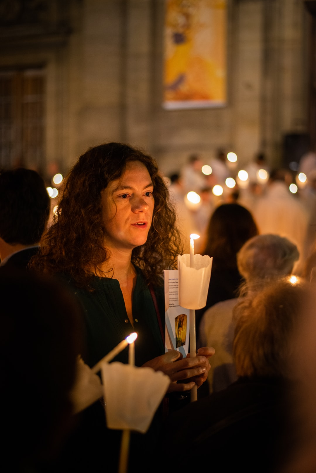Believer holding candle at evening church ceremony in Paris.