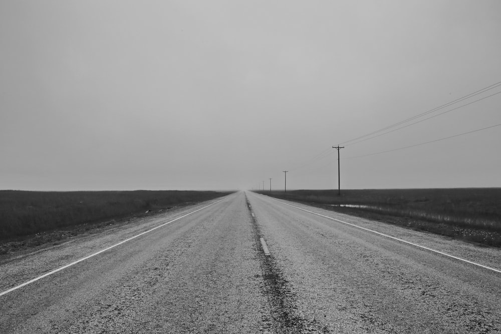 grayscale photo of road between grass field