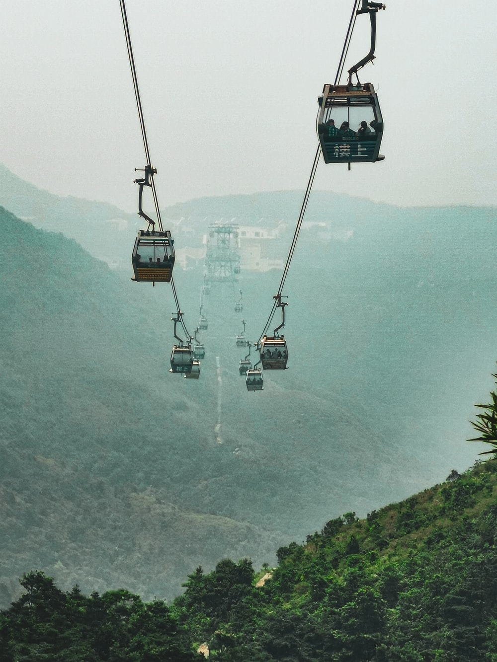 black cable car over green mountain during daytime