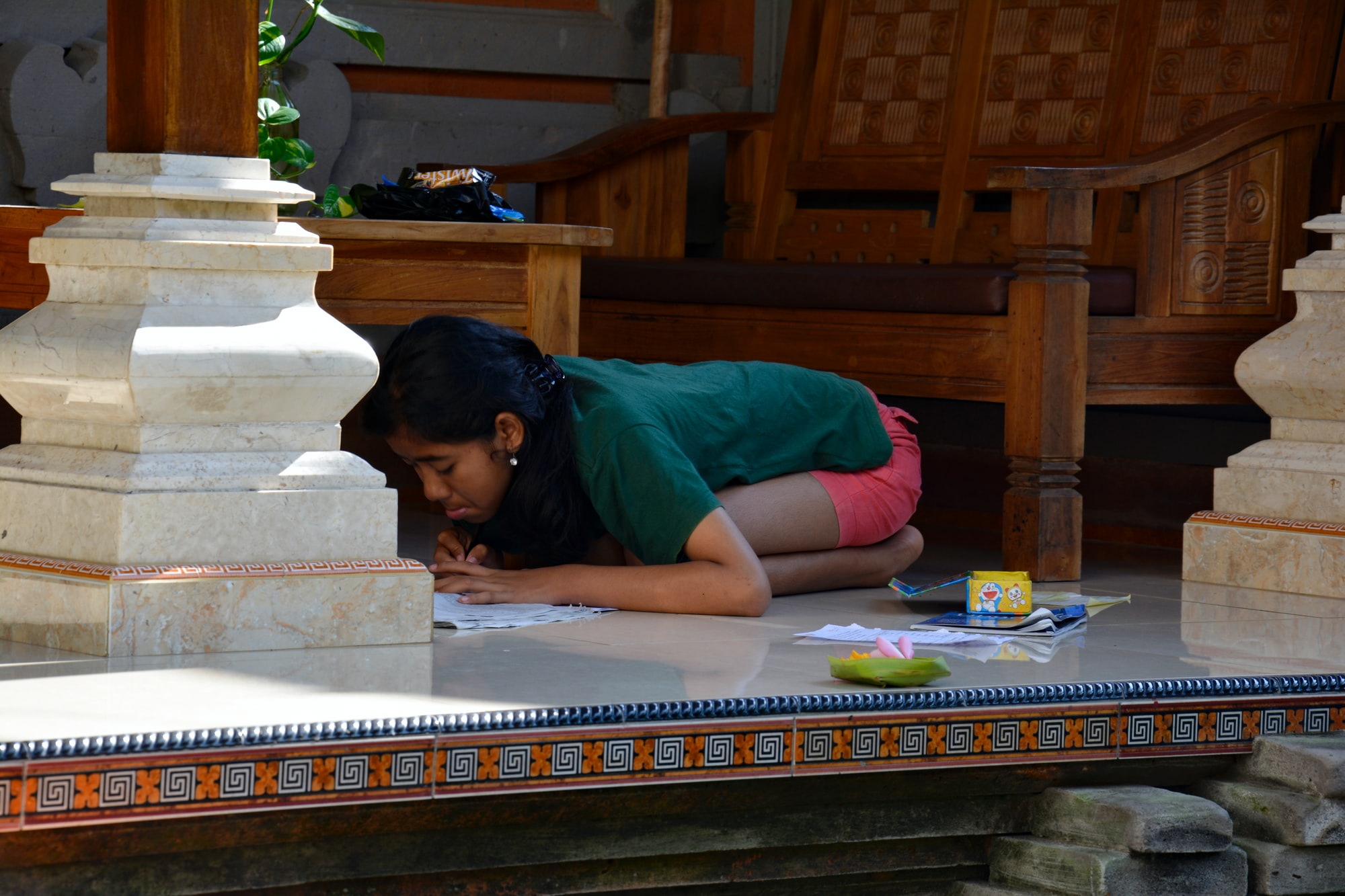 Balinese girl studying on a terrace