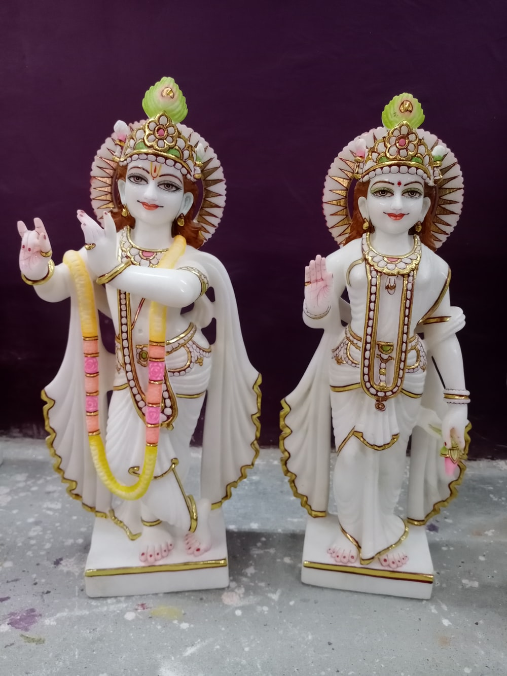 2 gold and red hindu deity figurines