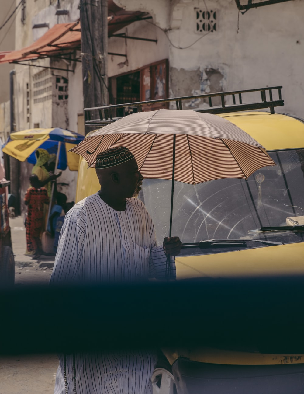 man in white and black striped dress shirt holding umbrella