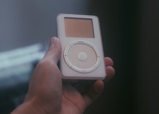 A 2nd generation iPod music player being held up by hand.