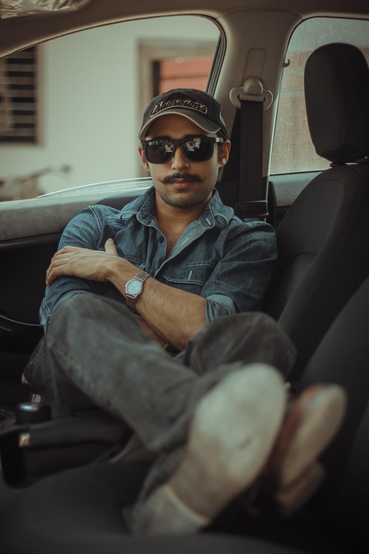 man in blue denim button up jacket wearing black sunglasses sitting on car seat