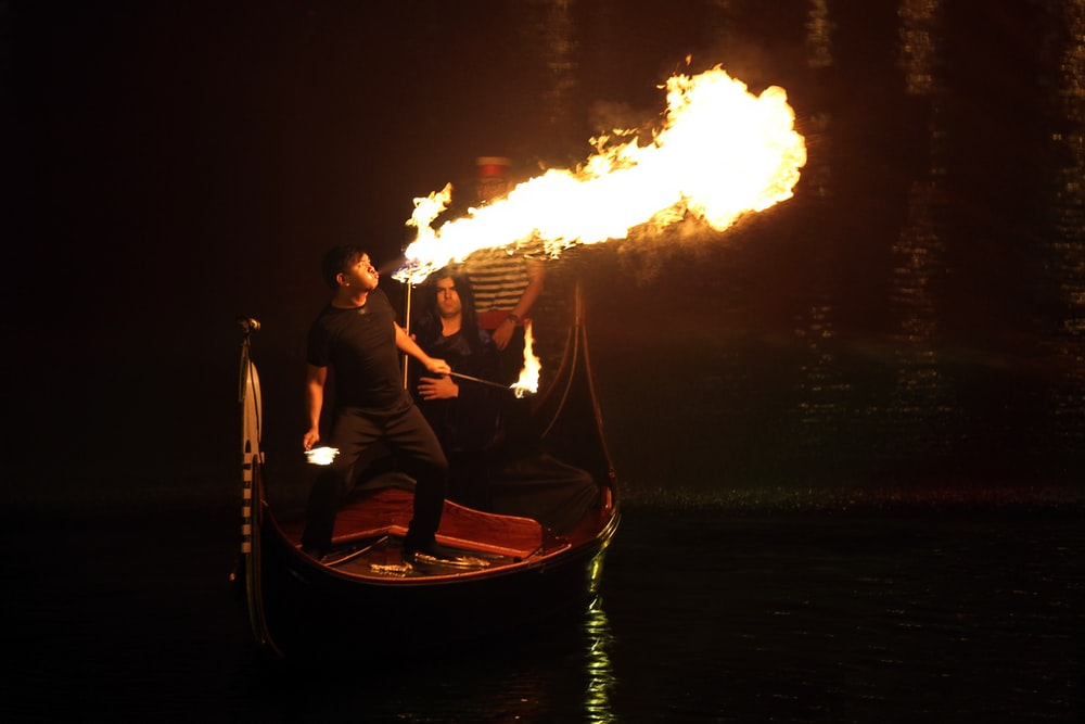man and woman on boat with fire