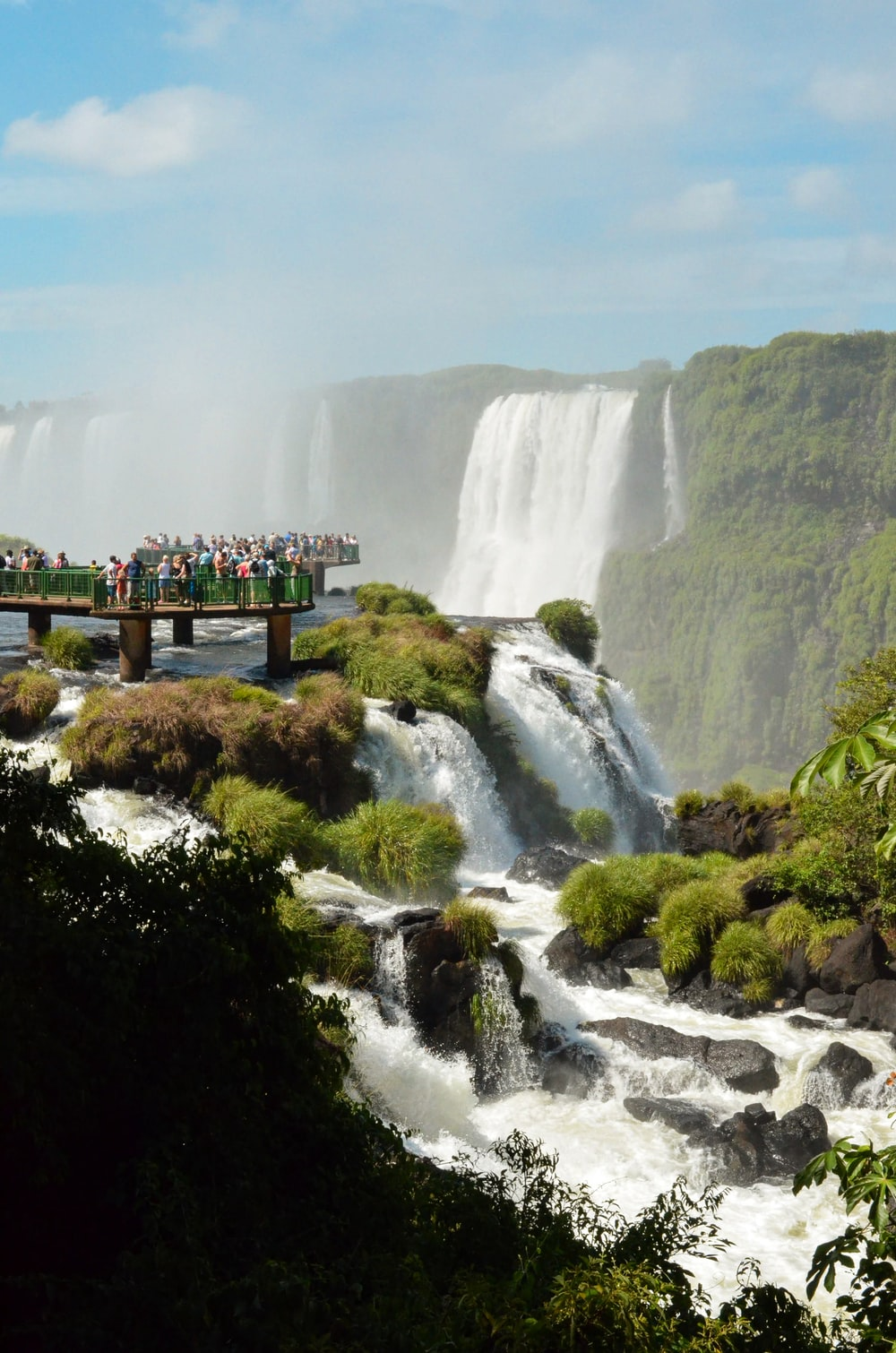 people standing on wooden bridge over waterfalls during daytime