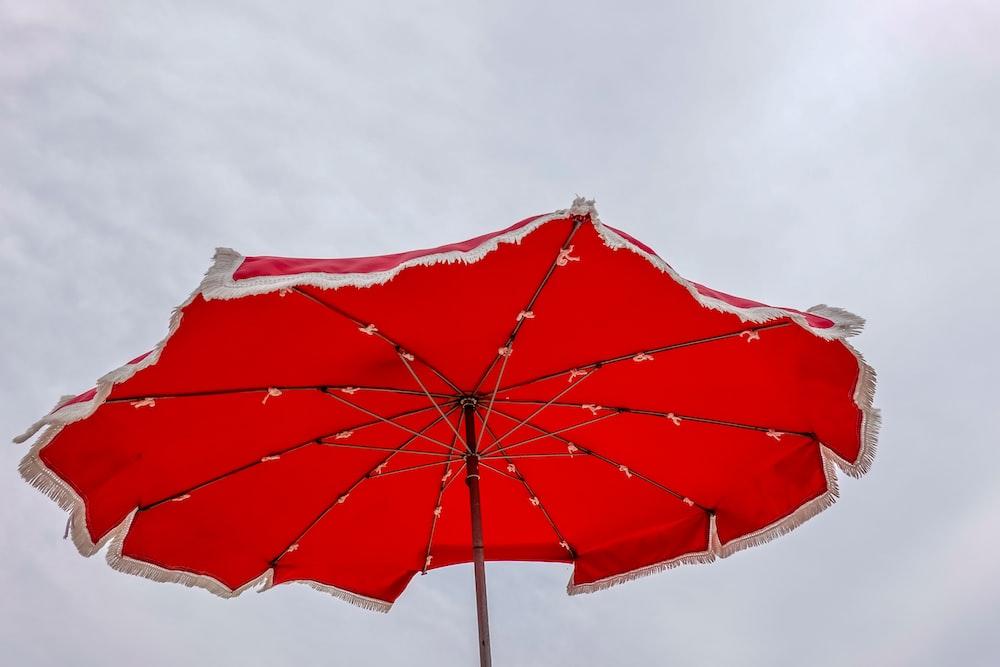 red umbrella under white sky