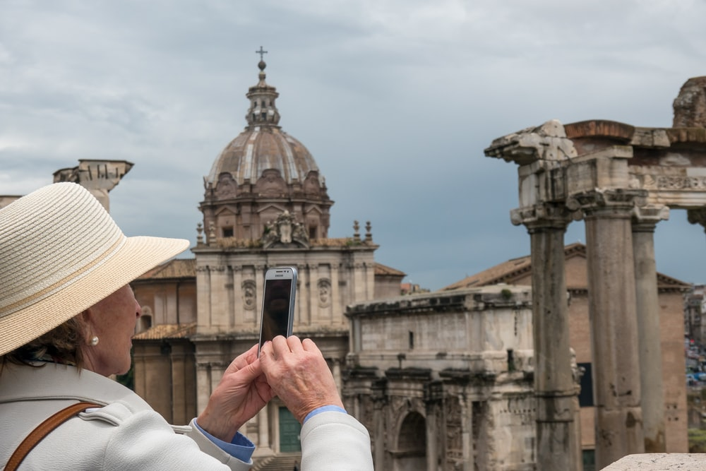 man in white long sleeve shirt holding smartphone