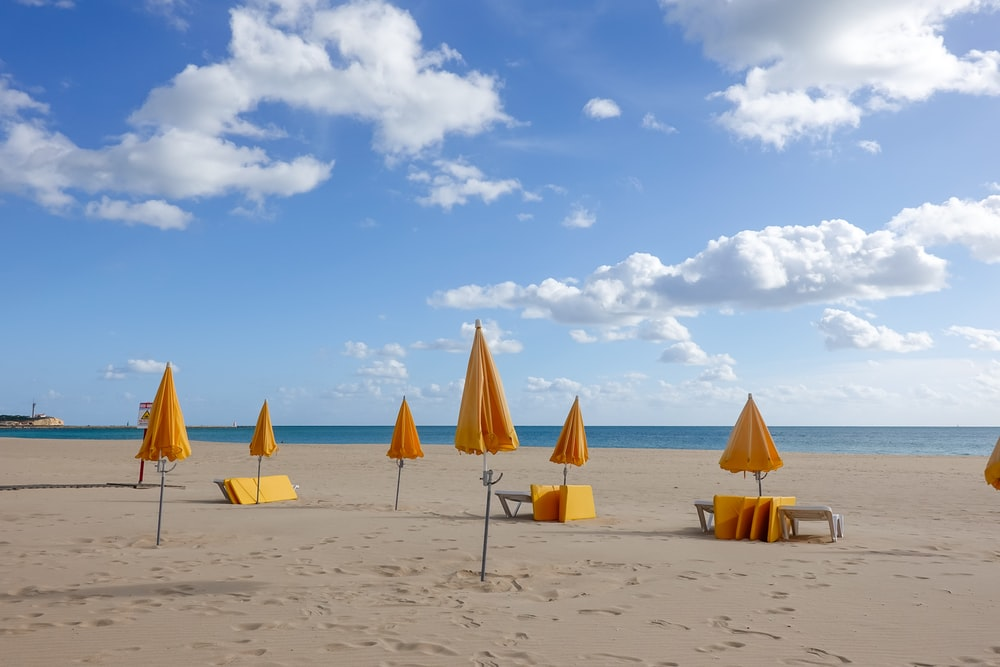 two brown and white beach umbrellas on beach during daytime