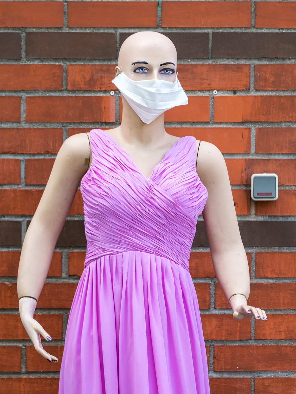 woman in purple tank top wearing white face mask