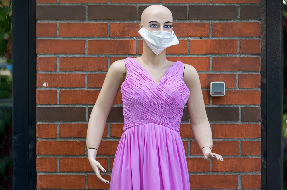 woman in purple sleeveless dress wearing white face mask