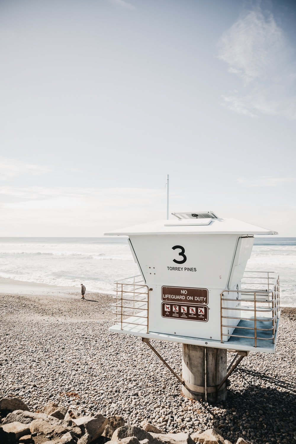 white lifeguard house on beach during daytime