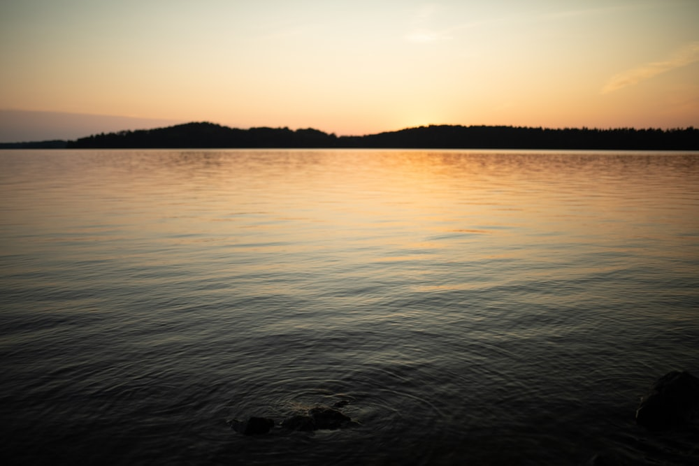 body of water near mountain during sunset