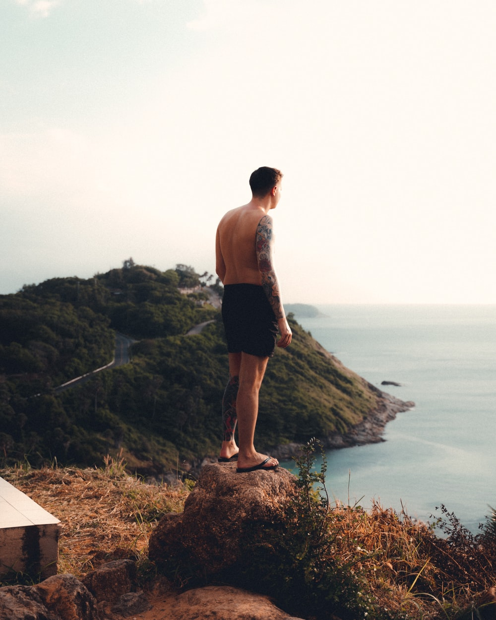 man in black shorts standing on brown rock near body of water during daytime