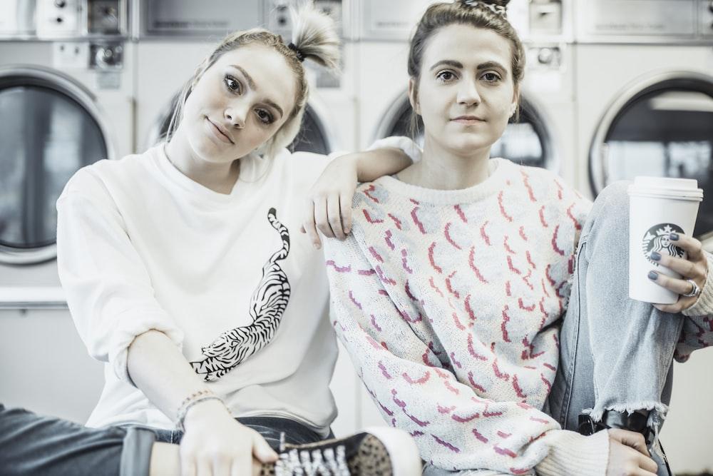 2 girls sitting on gray metal bench