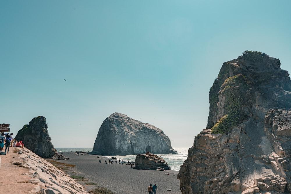 people walking on beach near rocky mountain during daytime
